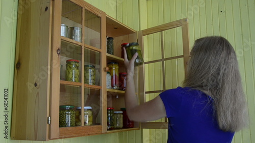 Girl take jar with pickled cucumber vegetable preserve from rack