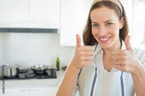 Smiling young woman gesturing thumbs up in kitchen