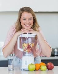 Woman preparing mix fruit juice in liquidizer