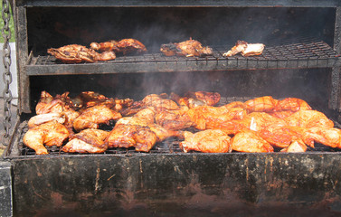 Chicken Portions Cooking on a Large Outdoor Barbeque.