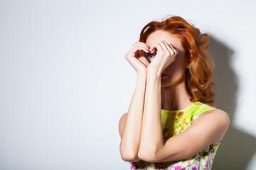 Girl doing hands binoculars.