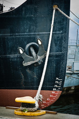 Nose of the moored ship with an anchor on a board