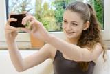 Teenager fotografiert Selfie mit Smartphone poster