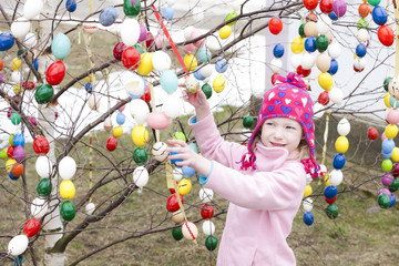 little girl standing by Easter tree