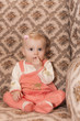 portrait of toddler girl sitting on armchair