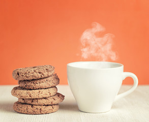 Oatmeal cookies and cup of coffee on wooden table