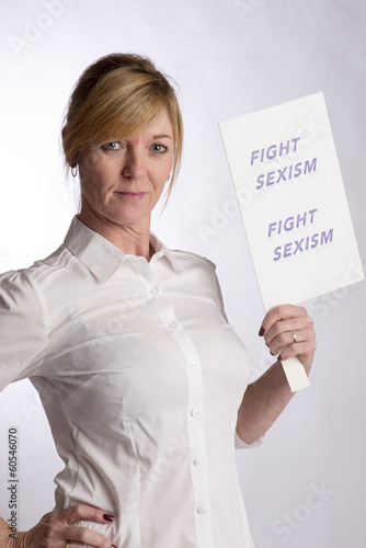 Mature female protester holding Fight Sexism poster