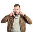 Handsome man covering his ears over white background