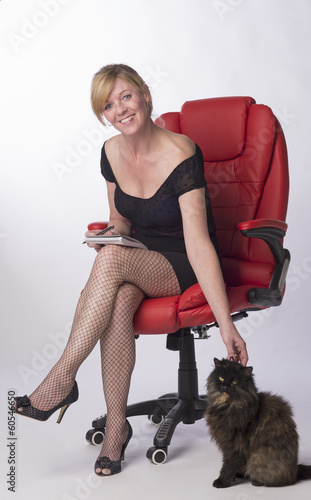 Secretary sitting on office chair stroking the office cat