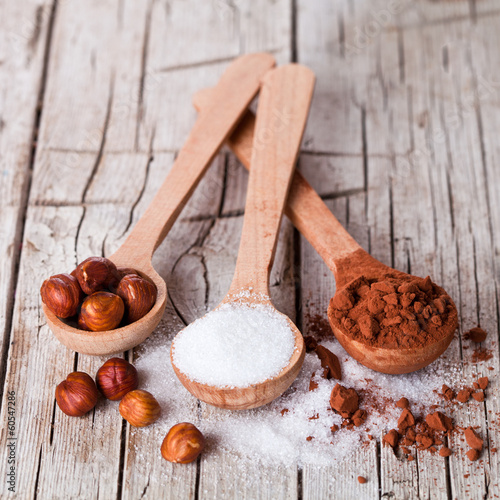 sugar, hazelnuts and cocoa powder in spoons