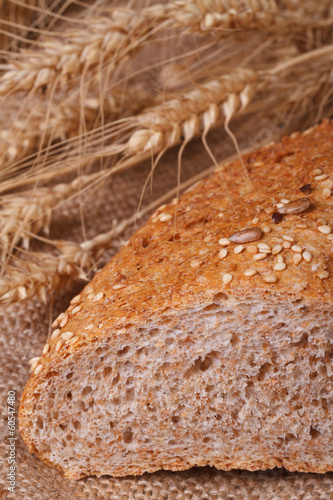 bread with sesame seeds and wheat spikelets close-up