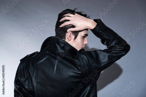 Cool retro rock and roll 50s fashion man. Hand in his hair. Wear