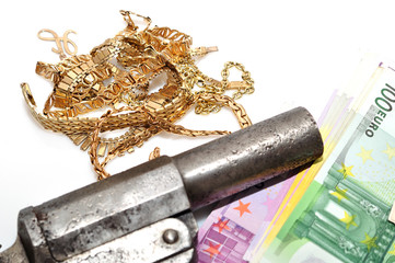 Gold money and a gun on white background.