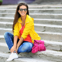 Beautiful young model girl in colorful clothes sitting on stairs