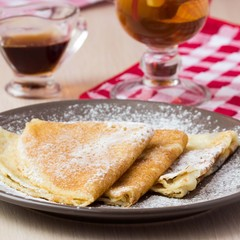 Thin sweet pancakes with powdered sugar for Shrovetide
