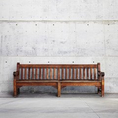 Antique bench on bright concrete background