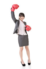 Happy smiling asian business woman with red boxing glove