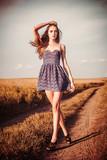 Beautiful girl in dress walking on the trai atl field