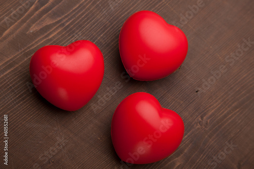 three red hearts on wooden background