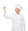 smiling female chef pointing finger to sonething
