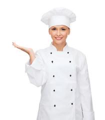 smiling female chef holding something on hand