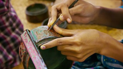 Burma. Artist makes pattern on the product in the workshop