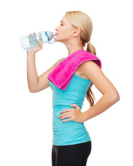 sporty woman with towel and watel bottle
