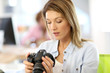 Woman reporter in office looking at photo camera