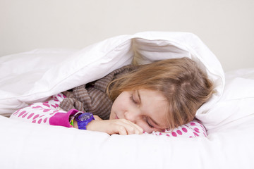 little girl sleeping peacefully in bed covered