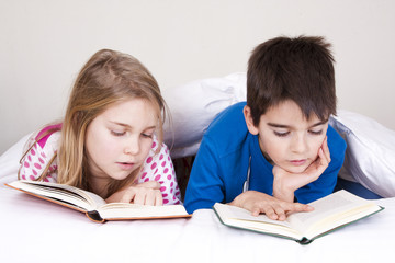couple of kids in bed covered with blanket reading