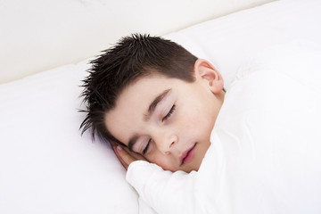 Little boy in bed covered with blanket