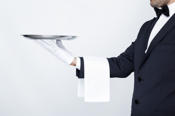 Professional waiter holding empty silver tray over gray backgrou