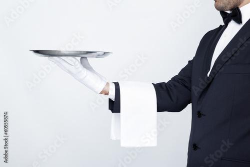 Leinwanddruck Bild Professional waiter holding empty silver tray over gray backgrou
