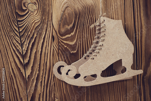 Pair of carton figure skates over wooden background