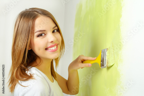 Beautiful girl painting a wall