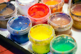 Colorful acrylic paints in plastic cans. Macro photo