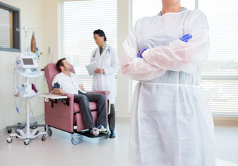 Nurse Standing Arms Crossed While Doctor Examining Patient's Hea