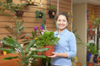 mature woman chooses primula in pot