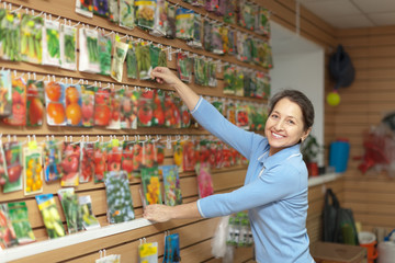 mature woman chooses packaged seeds