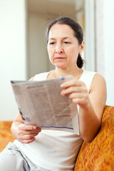 serious mature woman reads newspaper