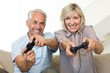 Cheerful mature couple playing video game on sofa