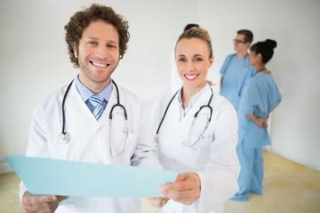 Happy doctors holding file