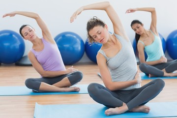 Women with eyes closed exercising at fitness studio