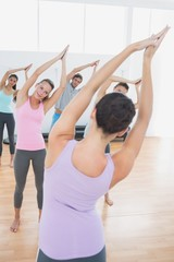 Sporty class with joined hands in fitness studio