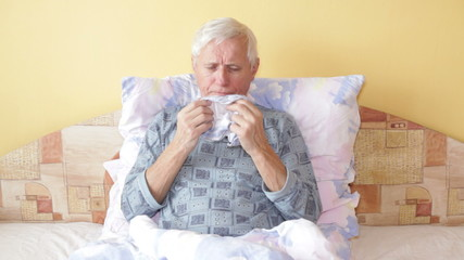 Sick senior man coughing and blowing his nose in bed.