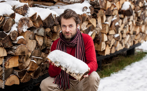 Smiling man with firewood - winter countryside landscape