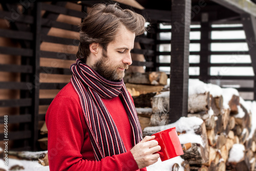 Man drinking hot tea outdoor - winter countryside landscape