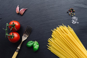 Pasta ingredients on black slate background