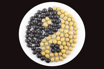 Yin and Yang made of green and black olives on the plate