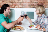 Couple toasting over a restaurant table